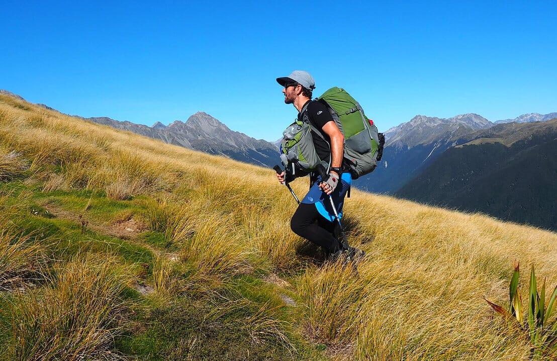Male hiker climbing slope wearning Aarn pack